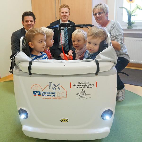 v.l.n.r Oliver Drave, Benedikt Kemmann und Birgit Schlottmann freuen sich mit den Kindern über den neuen Kinderbus